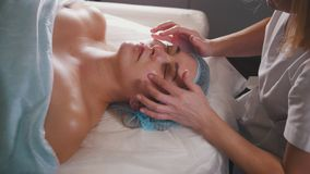 Woman doctor performes cosmetic procedure - mask facial massage at spa salon skincare. Close up Stock Photography