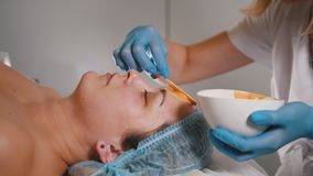 Woman doctor performes cosmetic procedure - mask facial massage at spa salon skincare. Close up stock video