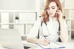 Woman doctor on the phone. Portrait of a woman doctor with red hair talking on the phone in her office and taking notes in a clipboard. Toned image stock illustration