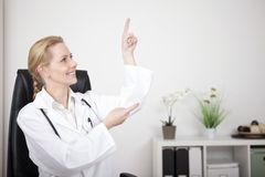 Woman Doctor Pointing and Looking to Upper Right Stock Images
