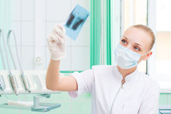 Woman doctor in protective mask looking at x-ray Royalty Free Stock Photography