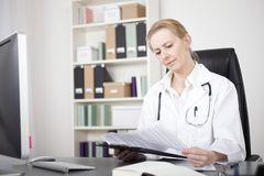 Woman Doctor Reading Medical Reports at her Office. Adult Woman Doctor Reading Medical Reports on a Clipping Board Seriously While Sitting at her Office royalty free stock photos