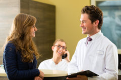 Woman and doctor at reception of clinic stock photos