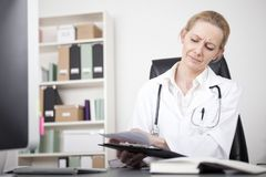 Woman Doctor Scanning Reports on a Clipping Board Royalty Free Stock Photography