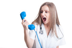 Woman doctor shouting at the phone Royalty Free Stock Image