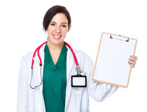 Woman doctor show with blank page of clipboard Stock Photos