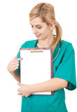 Woman doctor showing something on clipboard. Young woman doctor with stethoscope showing something on clipboard, white background Royalty Free Stock Images