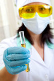 Woman doctor shows a test tube of yellow solution Stock Photos