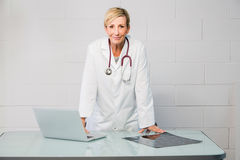 Woman doctor standing behind desk Royalty Free Stock Photography