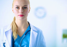 Woman doctor standing with stethoscope at hospital Stock Images