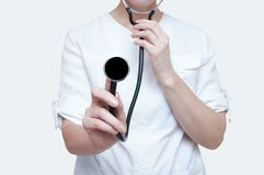 Woman doctor with a stethoscope in hands on white background. Isolate royalty free stock image