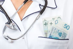 Woman doctor with stethoscope and polish currency money in apron pocket, corruption, bribe or paying for care concept Stock Photo