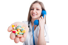 Woman doctor talking on the phone and offering pills Royalty Free Stock Image