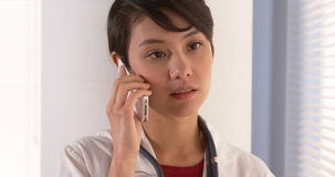Woman doctor talking on smartphone in office Stock Photography