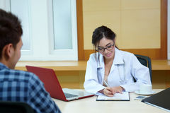 Woman doctor talking to her male patient at office Stock Image