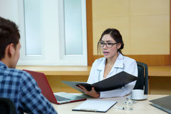 Woman doctor talking to her male patient at office Stock Images