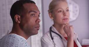 Woman doctor talking about xrays to black patient Stock Photography