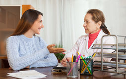 Woman doctor and teenager patient. Friendly female doctor and teenager patient at table Stock Image