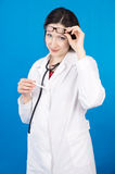 Woman doctor with a thermometer on a blue background Royalty Free Stock Photo
