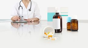 Woman doctor use digital tablet at the desk office with pills, drugs and medicine bottles, medical care concept, web banner. And copy space template royalty free stock photography