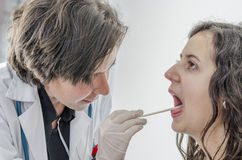 Woman doctor using a tongue depressor with girl patient. Royalty Free Stock Image