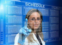 Woman doctor using a virtual touch screen interface with a calen Royalty Free Stock Images