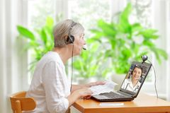Woman doctor video call instruction leaflet. Senior women sitting at a table in her living room with the instruction leaflet of her prescribed medication during royalty free stock images