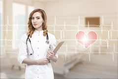 Woman doctor in a ward with cardiogram. Portrait of a red haired woman doctor standing in a hospital ward. There is a cardiogram and a heart sketch to the right stock photo
