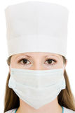 Woman doctor wearing a mask and hat royalty free stock photography