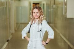 Woman doctor in a white coat in the corridor stock photos
