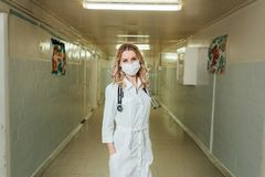 Woman doctor in a white coat in the corridor royalty free stock image