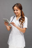 Woman doctor in the white medical uniform with a tablet in the hand Royalty Free Stock Image