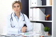 Woman doctor write prescription while sitting in hospital office. A lot of various colored pills liye at her clipboard. Medicine and health care Stock Photography