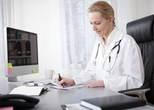 Woman Doctor Writing Findings at her Worktable Royalty Free Stock Photography