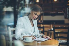 Woman with document. Young business woman writing on document at cafe royalty free stock photo