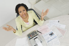 Woman With Documents And Expense Receipt. High angle view of a frustrated African American woman with documents and receipt expense at home Royalty Free Stock Image
