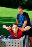 Woman does crunches with personal trainer Stock Photography