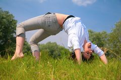 Woman does exercise on  grass Royalty Free Stock Photos