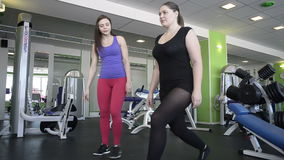 Woman does exercise under supervision of trainer stock video footage