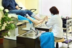 Woman does foot massage for man Royalty Free Stock Images