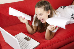 Woman does a great job thanks to the internet. Woman surfing the net at home, on red couch, and she success on finding information Royalty Free Stock Images