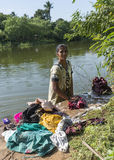 Woman does the laundry standing in the river. Stock Images