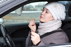 Woman does make up in car, looking at mirror Royalty Free Stock Images