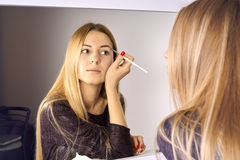 Woman does makeup before a mirror Stock Image