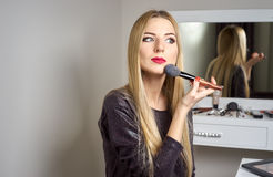 Woman does makeup before a mirror Stock Photo