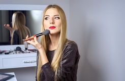 Woman does makeup before a mirror Stock Images