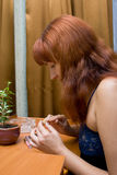Woman does manicure. The young woman in a dark blue peignoir does manicure Royalty Free Stock Photos