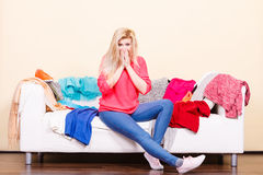 Woman does not know what to wear sitting on couch Royalty Free Stock Photo