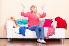 Woman does not know what to wear sitting on couch Stock Images