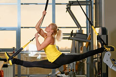 Woman does splits with trx fitness Royalty Free Stock Images
